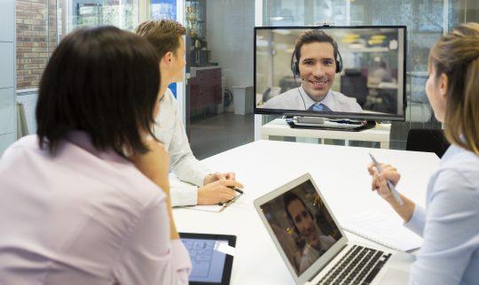 Det sitter tre mennesker rundt et møtebord med laptoper og ser på et digitalt møte på en skjerm