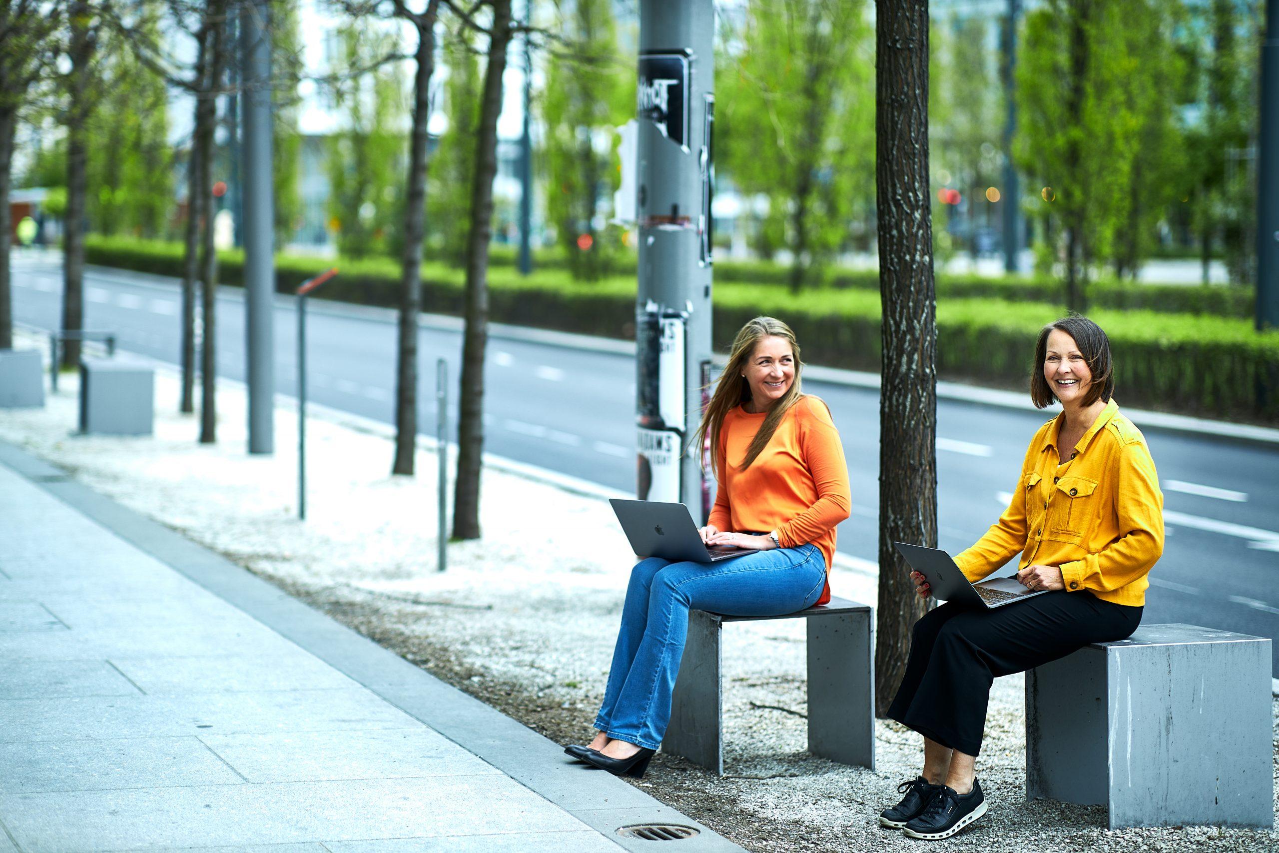 Benedicte og Sølvi Anne i CRED sitter på hver sin benk langs et fortau, med hver sin laptop i fanget